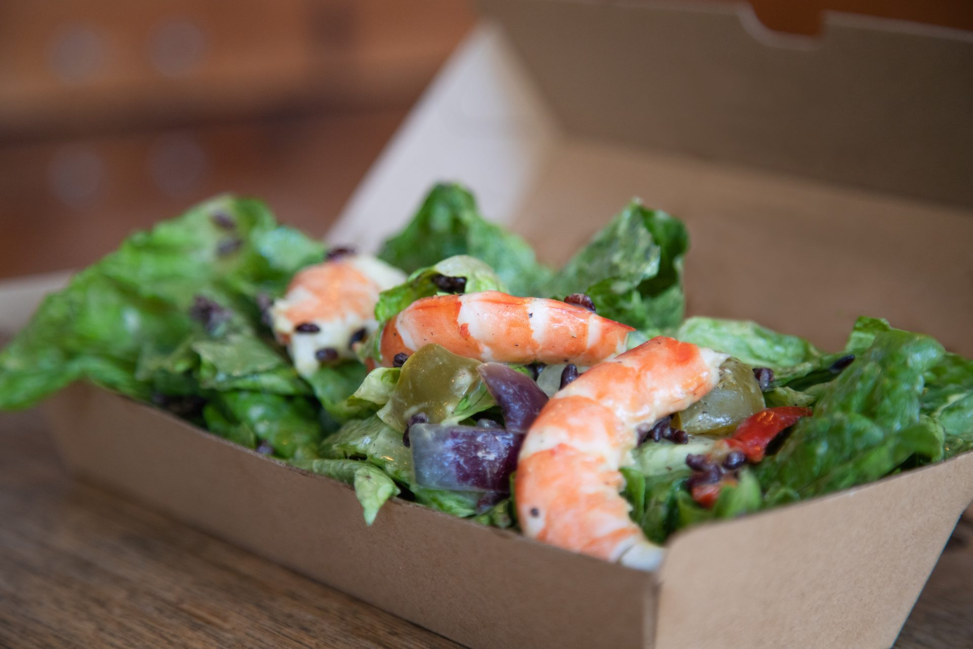 Our mason jar salads are tossed and then put into a kraft coloured takeaway box